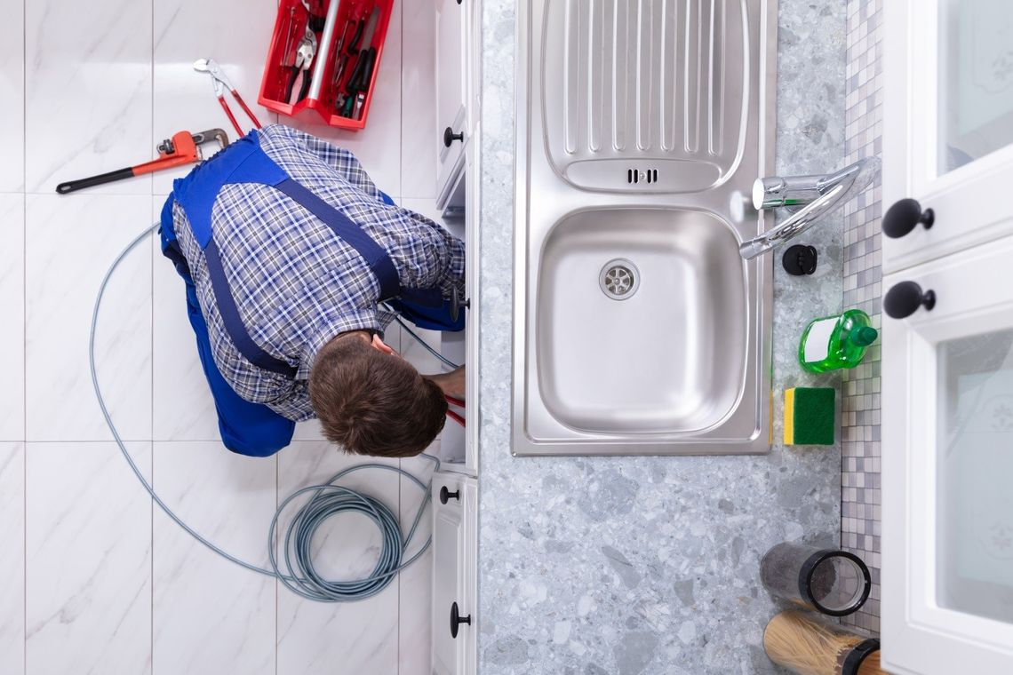 Man cleaning a drain in a kitchen